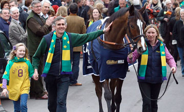 Clifford Baker holds hands with his daughter Charlotte as stable lass Rose Loxton leads championship race winner Kauto Star